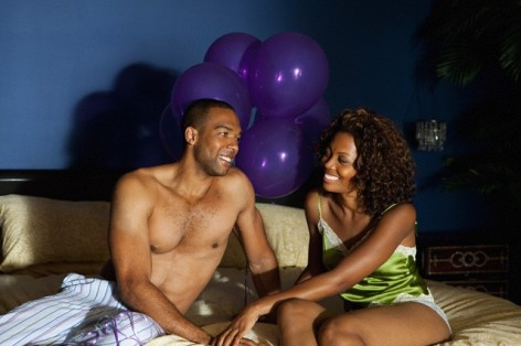 Young couple on bed with balloons in background