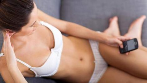 sexy young woman in underwear reading sms