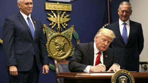 Le président américain Donald Trump signe un décret interdisant l'accès aux Etats-Unis pour les ressortissants de plusieurs pays musulmans, après la cérémonie d'investiture de son ministre de la Défense, le général James Mattis (à droite). © REUTERS/Carlos Barria