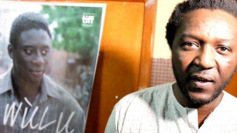 Le réalisateur malien Daouda Coulibaly. Sur l'affiche de « Wulu », l'acteur Ibrahim Koma qui incarne Ladji. Siegfried Forster / RFI
