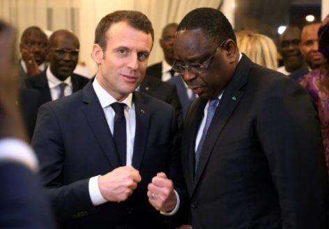 Le président français Emmanuel Macron (C-G) s'entretient avec son homologue sénégalais Macky Sall après son arrivé